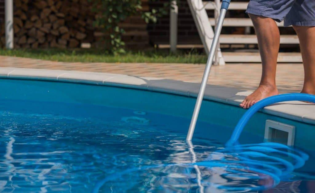 Photographie d'une homme nettoyant une piscine. Planète Eau Piscines, Construction, Rénovation, Entretien. Artisan pisciniste sur Aix en Provence et ses alentours.